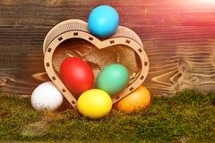 Bunte Eier Ostern im hölzernen Herzkasten Lizenzfreie Stockbilder