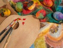 Bunte Eier Ostern mit den zwei Bürsten des Malers, einer hölzernen Palette und einem handgemalten Stoff Stockbild