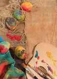 Bunte Eier Ostern mit den zwei Bürsten des Malers, einer hölzernen Palette und einem handgemalten Stoff Lizenzfreies Stockfoto
