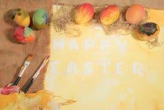 Bunte Eier Ostern mit den zwei Bürsten des Malers, Gewebe aus Jute, vereinbarten auf Gelb gemaltem Aquarellpapier Lizenzfreie Stockbilder