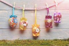 Bunte Eier Ostern verziert mit Thread, Perlen, die an der Wäscheklammer hängen Stockbilder