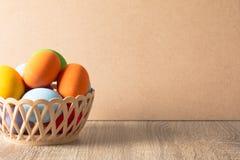 Bunte Eier werden in einen Korb auf einen Holztisch gelegt lizenzfreies stockbild