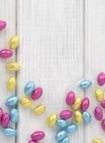Bunte eingewickelte Schokoladen-Ostereier zerstreuten auf weißes Brett-Hintergrund mit Raum oder Raum für Text, Kopie oder Wörter. Lizenzfreies Stockbild