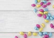 Bunte eingewickelte Schokoladen-Ostereier zerstreuten auf weißes Brett-Hintergrund mit Raum oder Raum für Text, Kopie oder Wörter. lizenzfreie stockbilder