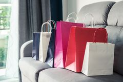 Bunte Einkaufstaschen auf Sofa lizenzfreie stockfotografie