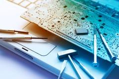 Bunte elektronische Brett- und Werkzeugreparaturen auf altem Laptop, getontes vibrierendes Konzept Stockbild