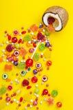 Bunte Explosion von Süßigkeiten in der Kokosnuss auf Gelb färbte Hintergrund, kreatives Stillleben, flache Lageart Stockfoto