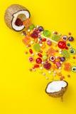 Bunte Explosion von Süßigkeiten in der Kokosnuss auf Gelb färbte Hintergrund, kreatives Stillleben, flache Lageart Lizenzfreies Stockfoto
