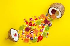 Bunte Explosion von Süßigkeiten in der Kokosnuss auf Gelb färbte Hintergrund, kreatives Stillleben, flache Lageart Lizenzfreie Stockfotografie