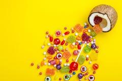 Bunte Explosion von Süßigkeiten in der Kokosnuss auf Gelb färbte Hintergrund, kreatives Stillleben, flache Lageart Lizenzfreie Stockbilder
