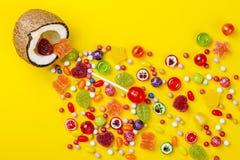Bunte Explosion von Süßigkeiten in der Kokosnuss auf Gelb färbte Hintergrund, kreatives Stillleben, flache Lageart Stockbilder