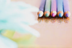 Bunte Eyeliners/Bleistifte mit den unfocused Blumenblättern Stockbild