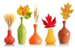 Bunte Fallblätter und -weizen in den Vasen Stockfotografie