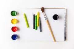 Bunte Farben, Zeichenstifte und Bürsten, die auf Kunstalbum liegen Stockfoto