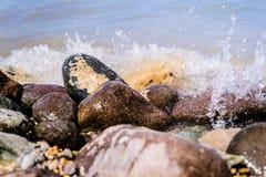Bunte Felsen mit dem Spritzen bewegt auf einen Strand wellenartig Stockfotografie