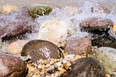 Bunte Felsen mit dem Spritzen bewegt auf einen Strand wellenartig Lizenzfreies Stockbild
