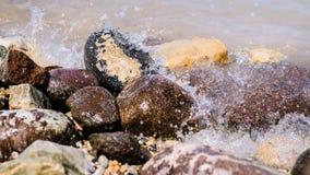 Bunte Felsen mit dem Spritzen bewegt auf einen Strand wellenartig Stockbilder