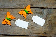 Bunte felty Schmetterlinge mit leeren Zeichen auf Holztisch Stockfoto