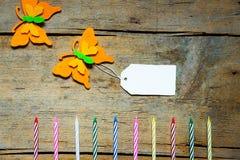 Bunte felty Schmetterlinge und Kerzen mit einem Zeichen auf hölzernem Vorsprung Stockbilder