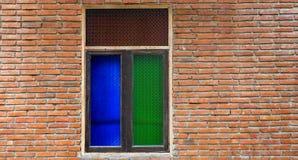 Bunte Fenster auf Backsteinmauer Stockbilder