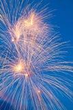 Bunte Feuerwerke auf dem blauen bewölkten Himmel Lizenzfreies Stockfoto