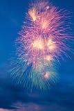 Bunte Feuerwerke auf dem blauen bewölkten Himmel Stockbilder