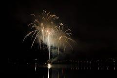 Bunte Feuerwerke stellen mit den Raketen dar, die über dem See bersten Stockfoto