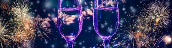 Bunte Feuerwerke und zwei Gläser von Champagner mit Blasennahaufnahme auf dem fallenden Schneehintergrund sprudeln stockfotografie