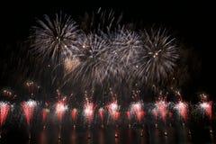 Bunte Feuerwerksexplosion, neues Jahr, Feuerwerke, orange erstaunliche Feuerwerke oben lokalisiert im dunklen Hintergrundabschluß Stockfoto