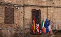 5 bunte Flaggen auf Ziegelstein in Italien Stockfotografie