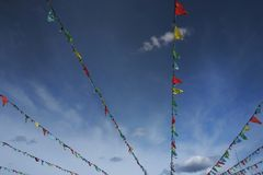 Bunte Flaggen, die gegen blauen Himmel mit dem Kopfe stoßen lizenzfreie stockfotos