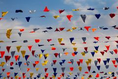 Bunte Flaggen, die gegen blauen Himmel mit dem Kopfe stoßen stockfoto