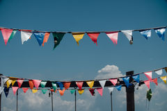 Bunte Flaggen, die gegen blauen Himmel mit dem Kopfe stoßen lizenzfreies stockfoto