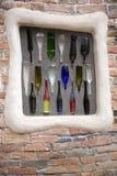 Bunte Flaschen eingebettet in Backsteinmauer Lizenzfreie Stockfotos