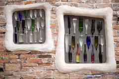 Bunte Flaschen eingebettet in Backsteinmauer Stockbilder