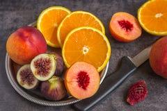 Bunte frische Früchte - Feigen, Orangen und Pfirsiche auf einer Dunkelheitsrückseite Stockbild