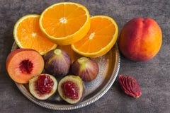 Bunte frische Früchte - Feigen, Orangen und Pfirsiche auf einer Dunkelheitsrückseite Lizenzfreie Stockfotos