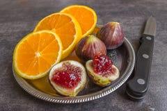 Bunte frische Früchte - Feigen, Orangen und Pfirsiche auf einer Dunkelheitsrückseite Lizenzfreies Stockbild