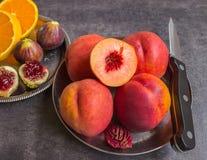 Bunte frische Früchte - Feigen, Orangen und Pfirsiche auf einer Dunkelheitsrückseite Stockfotografie
