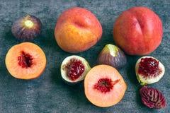 Bunte frische Früchte - Feigen und Pfirsiche auf dem dunklen Hintergrund Lizenzfreies Stockfoto