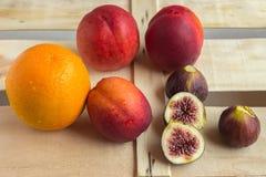 Bunte frische Früchte - Orangen, Feigen und Pfirsiche liegen auf einem woode Stockbilder