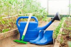 Bunte Gartenhilfsmittel Gießkanne, Gummistiefel und Rührstange Stockfotografie
