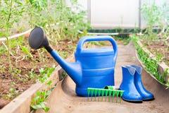 Bunte Gartenhilfsmittel Gießkanne, Gummistiefel und Rührstange Lizenzfreie Stockfotografie