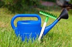 Bunte Gartenwerkzeuge, blaue Plastikgießkanne Lizenzfreie Stockbilder