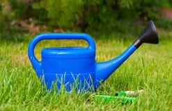 Bunte Gartenwerkzeuge, eine blaue Plastikgießkanne Stockfotos