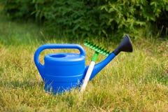 Bunte Gartenwerkzeuge, eine blaue Plastikgießkanne und Rührstange Stockfotografie