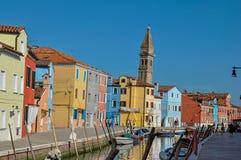 Bunte Gebäude, Turm, Leute und Boote vor einem Kanal bei Burano Stockfotos