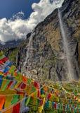 Bunte Gebets-Flaggen vor heiligem buddhistischem Wasserfall Lizenzfreie Stockbilder