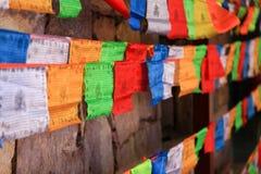 Bunte Gebetsflaggen mit hölzerner Wand im Hintergrund, Shangri-La Lizenzfreies Stockbild