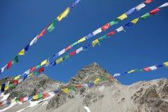 Bunte Gebetsflaggen und -Bergspitze gegen blauen Himmel Stockfoto